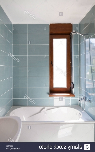 Image of Vertical Bathtub Vertical Shot Of Light Bathtub In A Bathroom With Window Stock